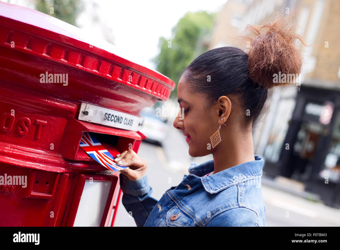 young woman sending a postcard in England Stock Photo