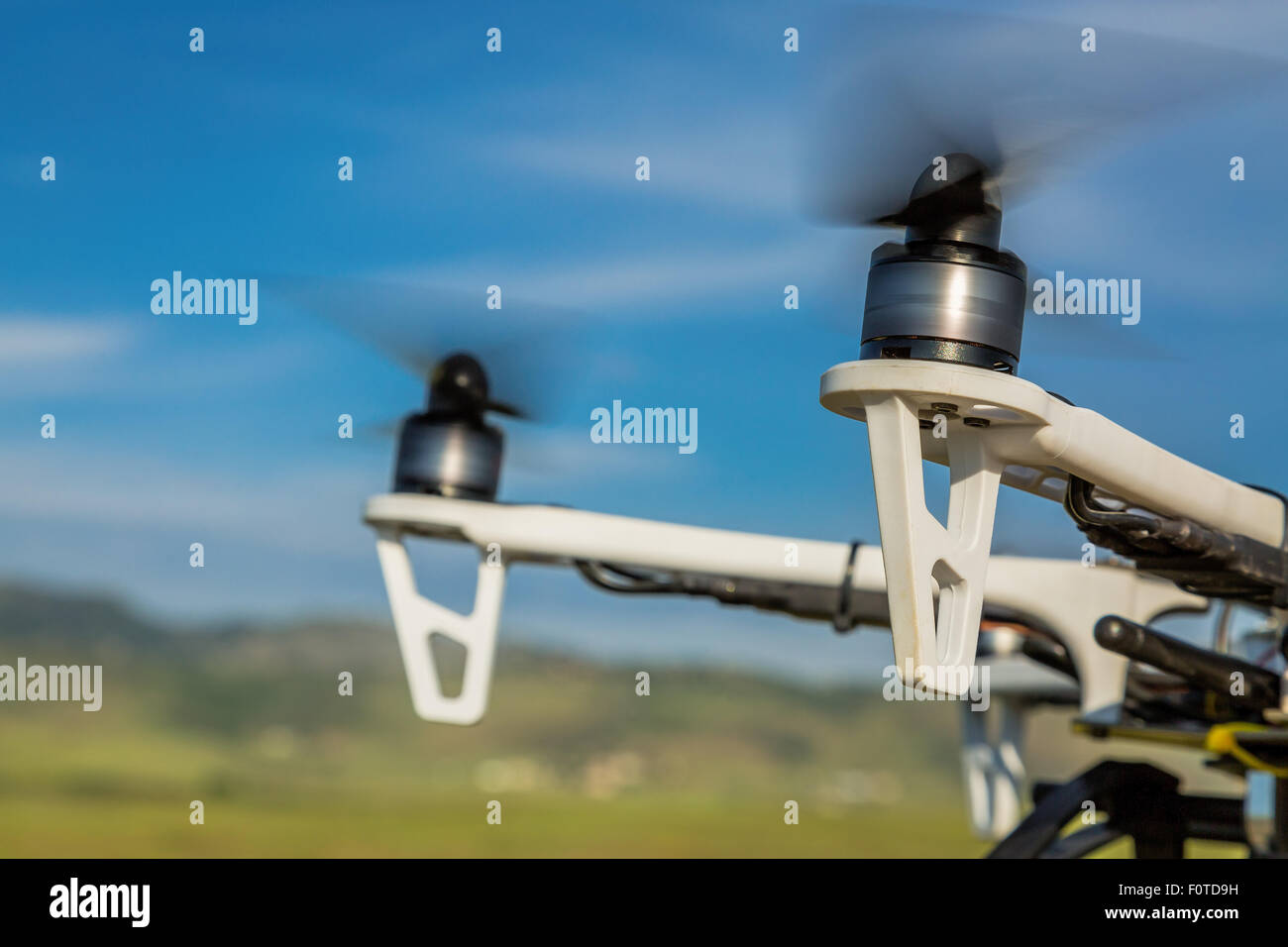 blurred spinning propellers of a hexacopter drone flying over rolling  prairie - Stock Image