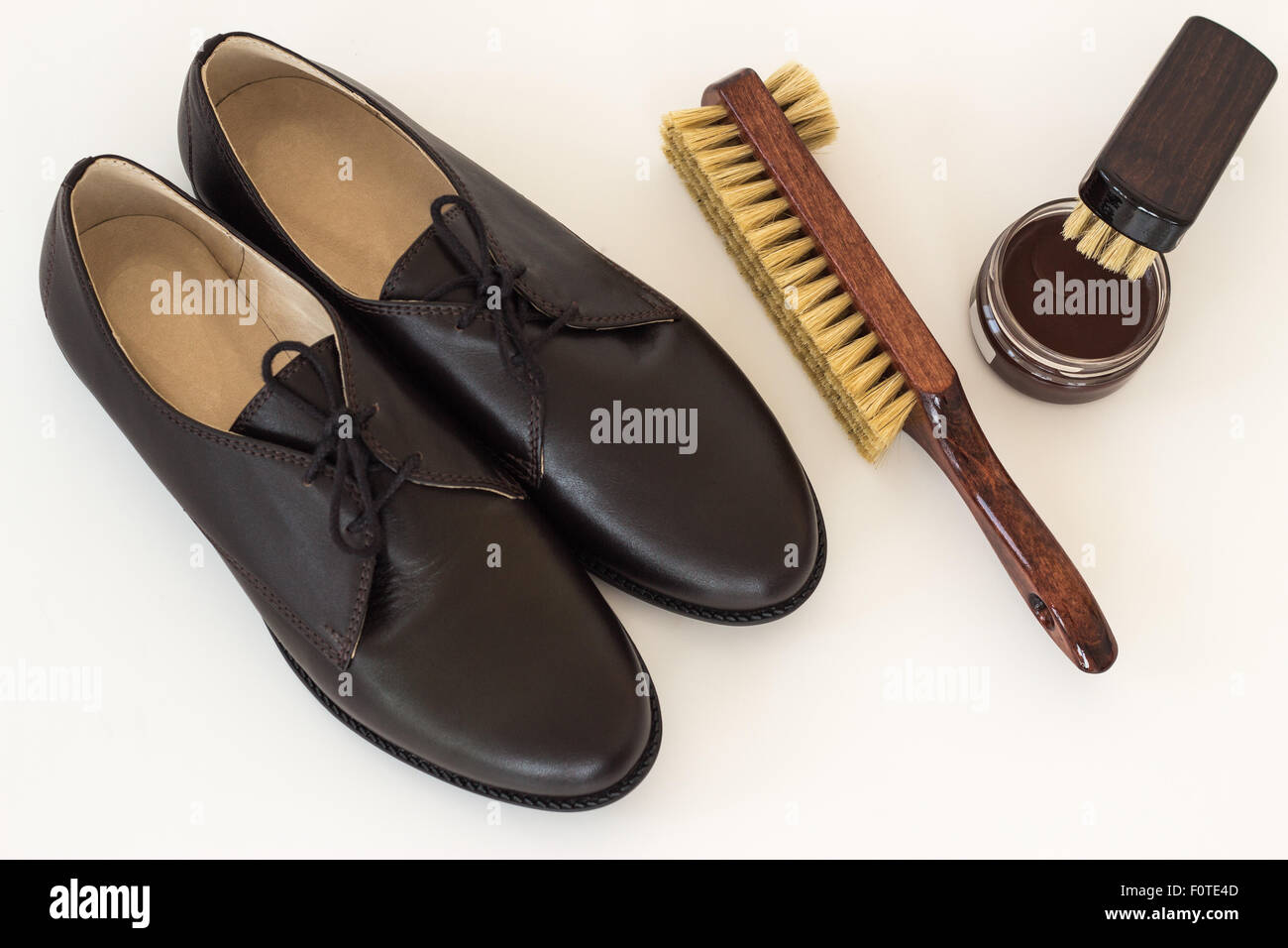 Isolated brown shoes and means on care of footwear - shoe-polish and brush - Stock Image