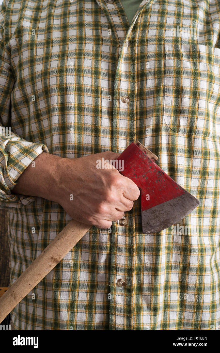 foreground lumberjack with an ax in his hand - Stock Image