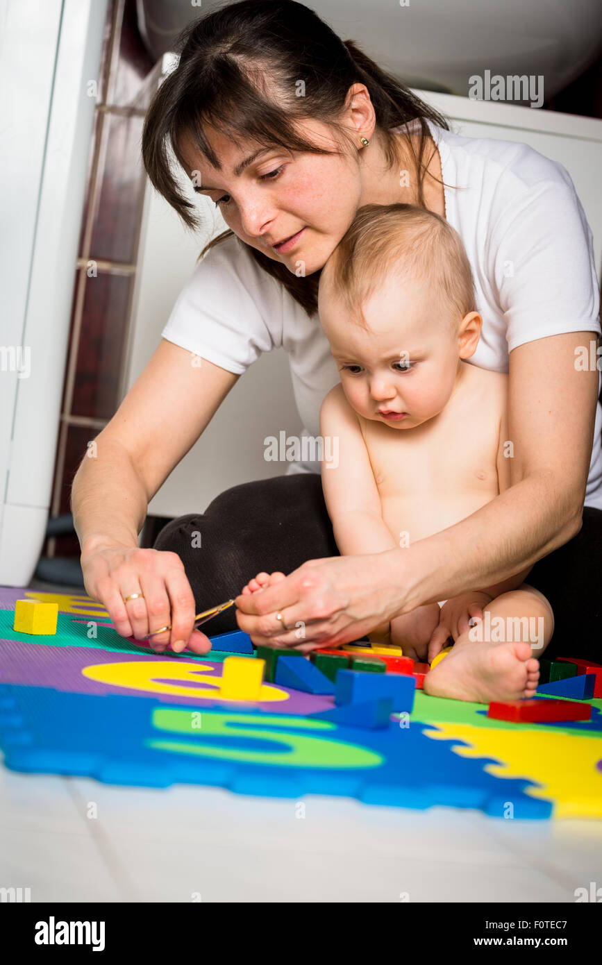 Mother cutting nails on feet of her baby - sitting on floor in bathroom - Stock Image