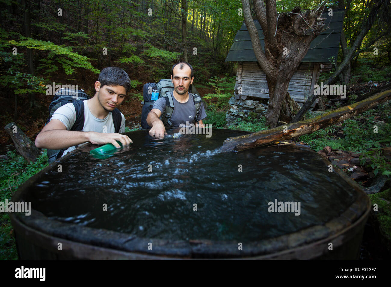 Hikers replenishing their water supplies at an old mill in the forest outsde the village of Isverna. Geoparcul Platoul - Stock Image