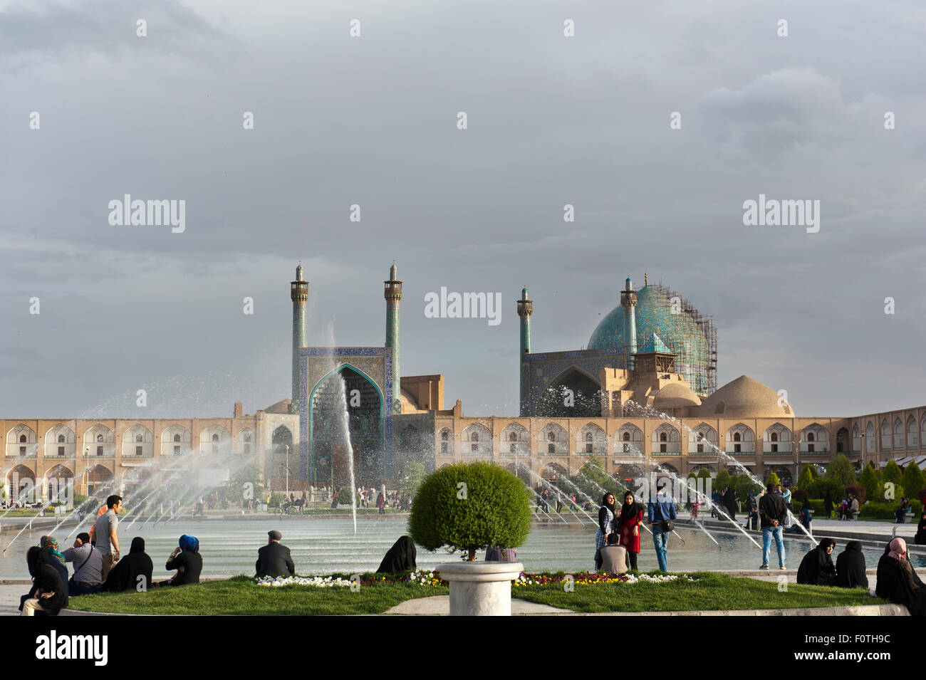 Iranians on the Maidan Square, also Naqsh-e Jahan Square, with a fountain, King Mosque with arches, Imam Mosque - Stock Image