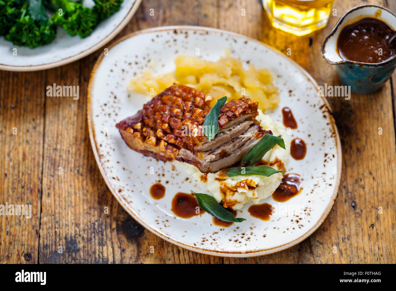 Pork belly with crackling, mashed potatoes, apple sauce and deep fried sage leaves - Stock Image