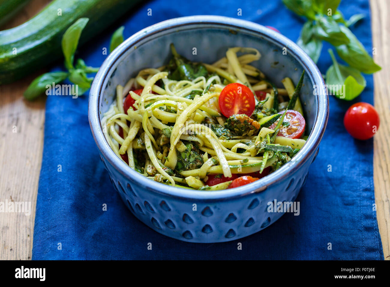 Zucchini spaghetti with cherry tomatoes and basil pesto - Stock Image