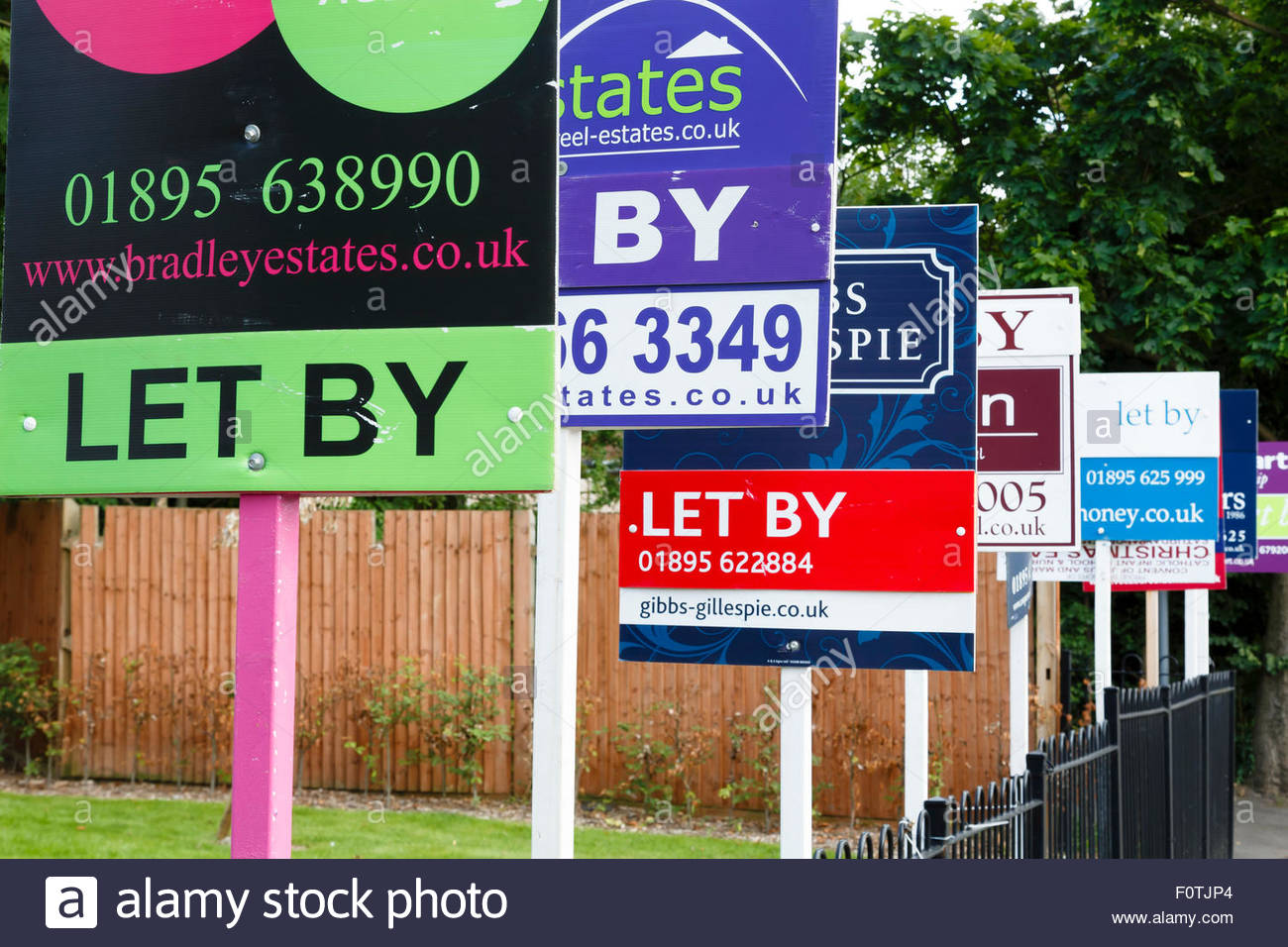 To let estate agent signs in a row advertising property in UK - Stock Image