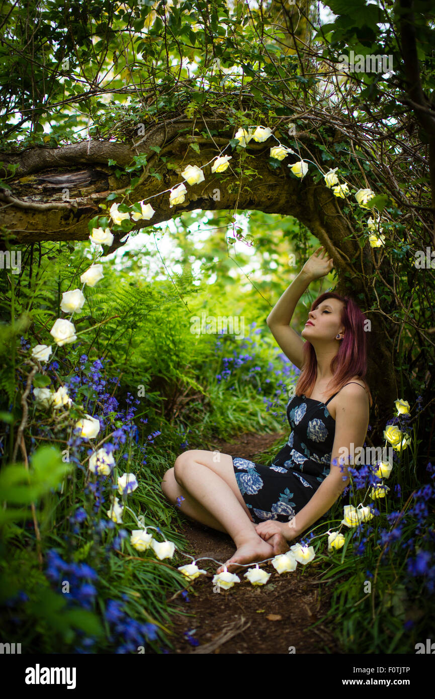 Fairytale fantasies: A young woman teenage girl alone by herself sitting down wearing a dress in woodland surrounded Stock Photo