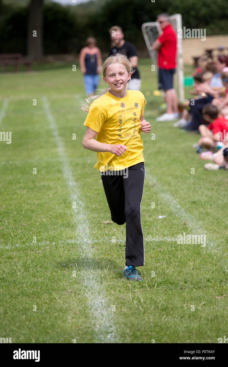 Young girl winning sprint race School Sports Day Chipping Campden UK - Stock Image