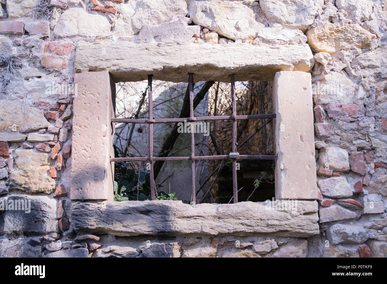 old window grille of a ruined castle in Italy Stock Photo