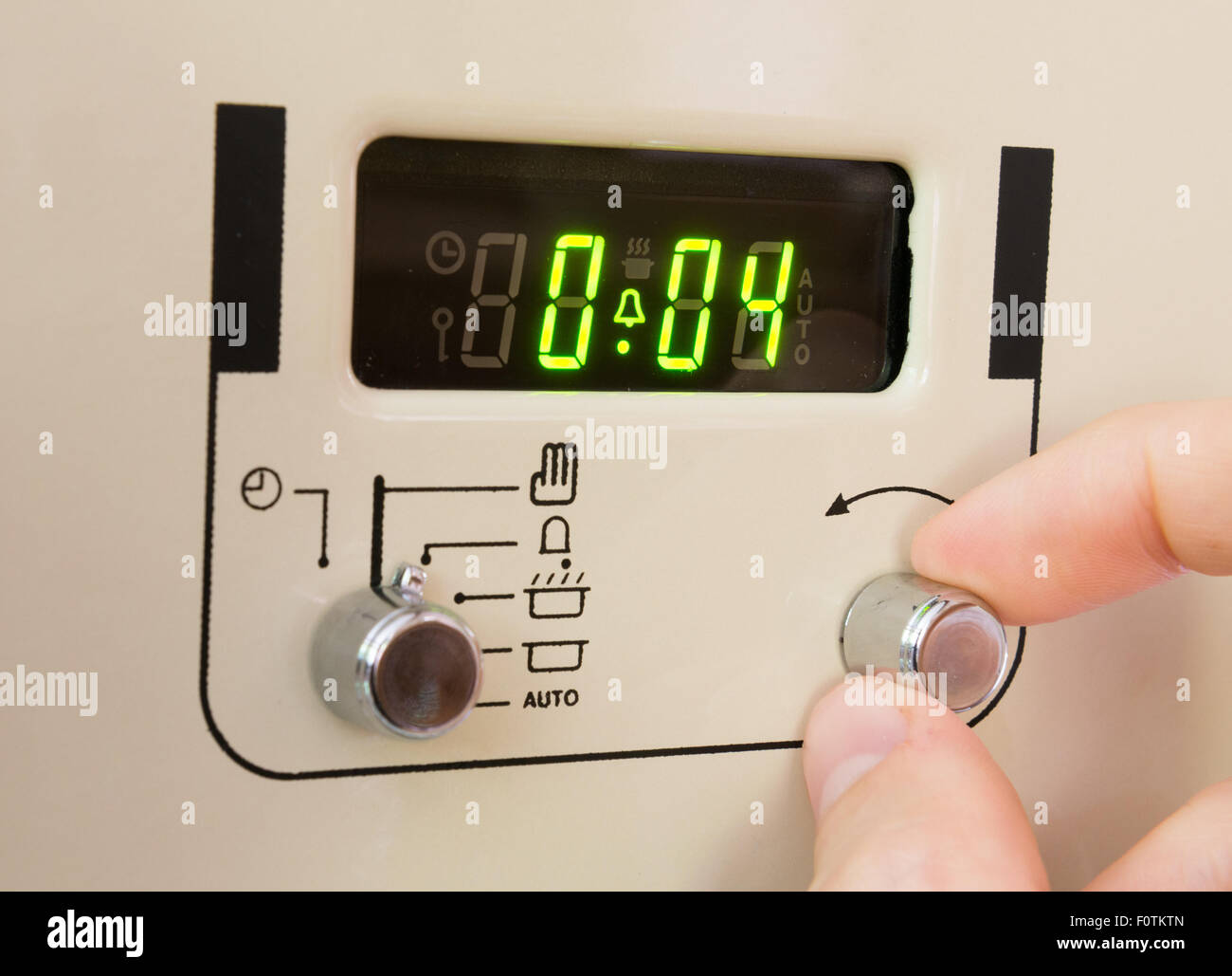 Setting a cooker timer to 4 minutes - Stock Image