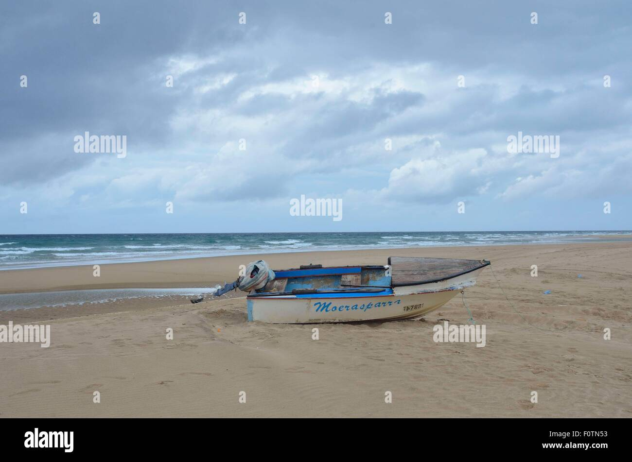 Old dilapidated fishing boats lying on the beach at Inhambane, Mozambique. These are unsafe and home repaired but - Stock Image