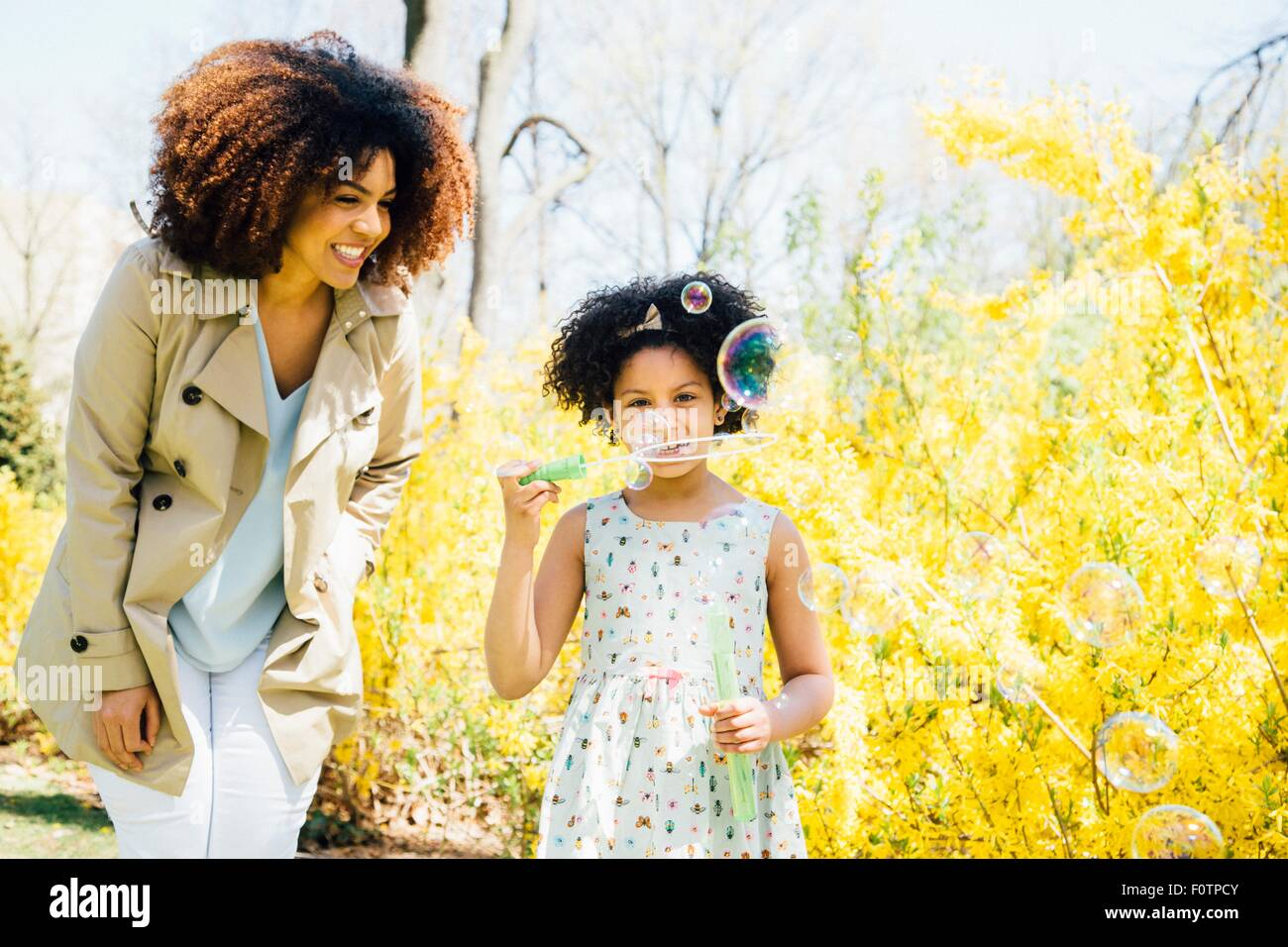 Front view of mother and daughter blowing bubbles - Stock Image