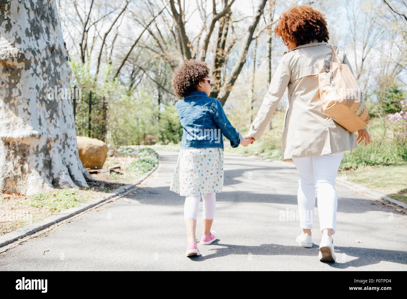 Full length rear view of mother and daughter walking holding hands - Stock Image