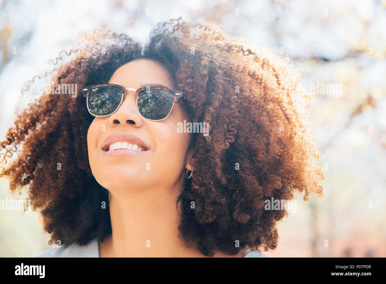 Close up portrait of mid adult woman, wearing sunglasses, smiling, looking away - Stock Image