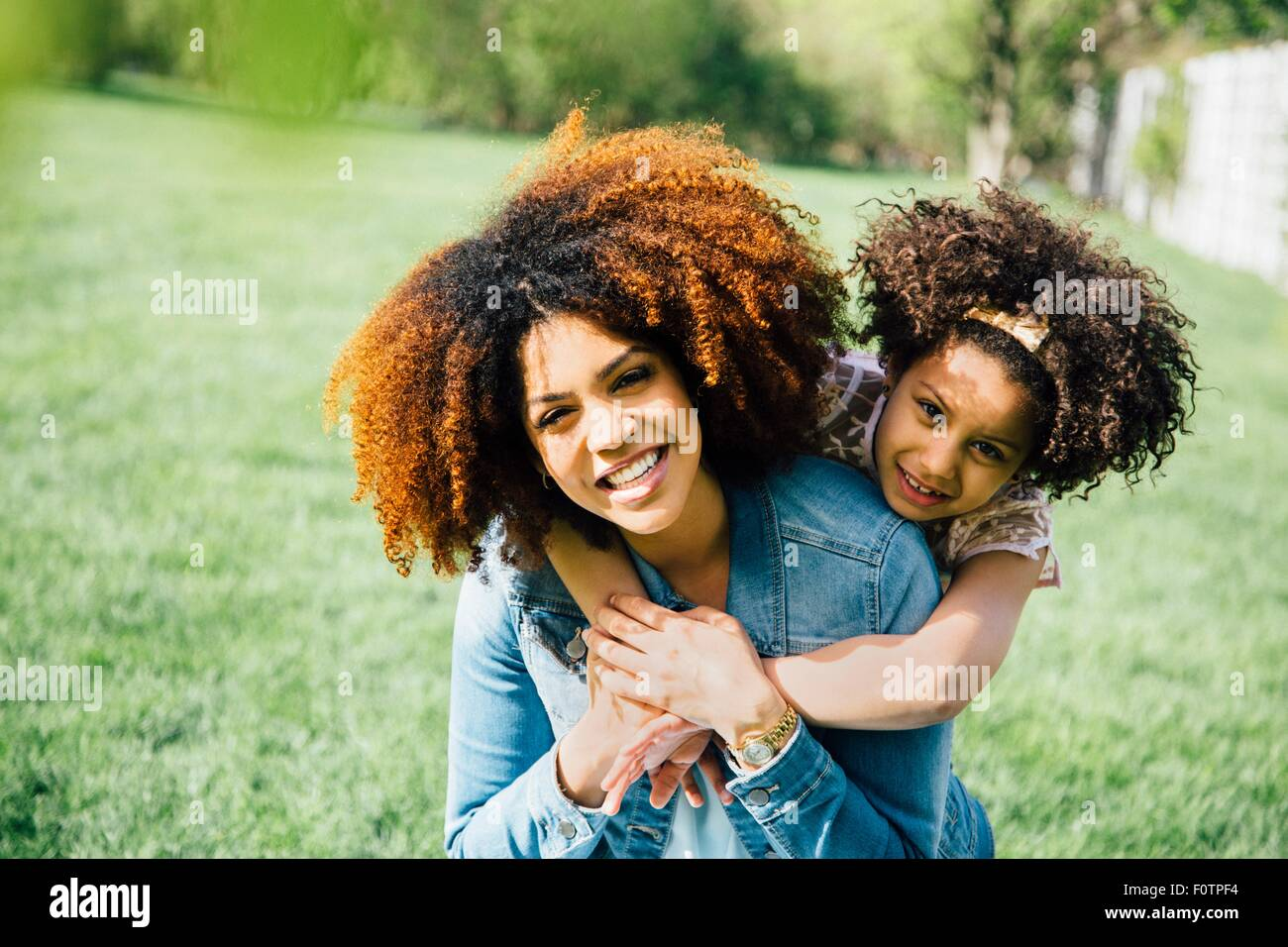 Daughter standing behind mother, arms around neck, smiling - Stock Image