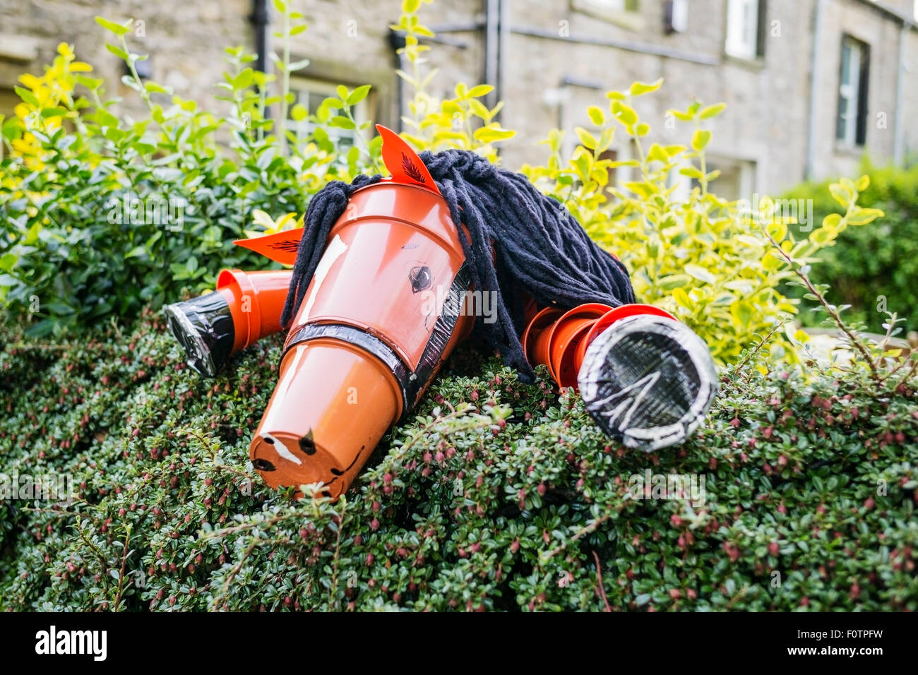 A flowerpot horse peering over a garden hedge in Settle, Yorkshire Dales National Park, England, UK - Stock Image