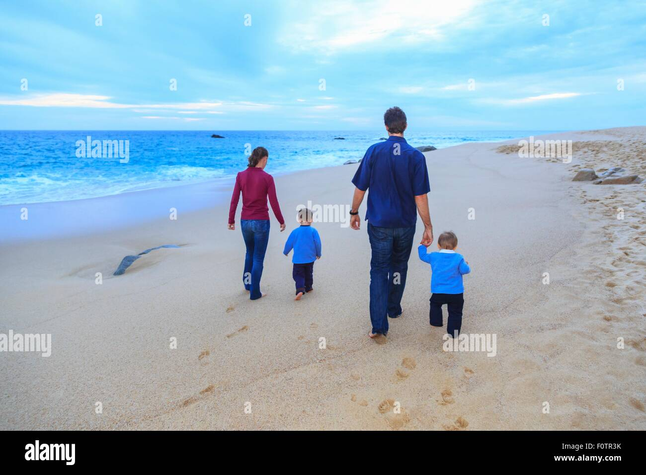 Young family walking on beach, rear view Stock Photo
