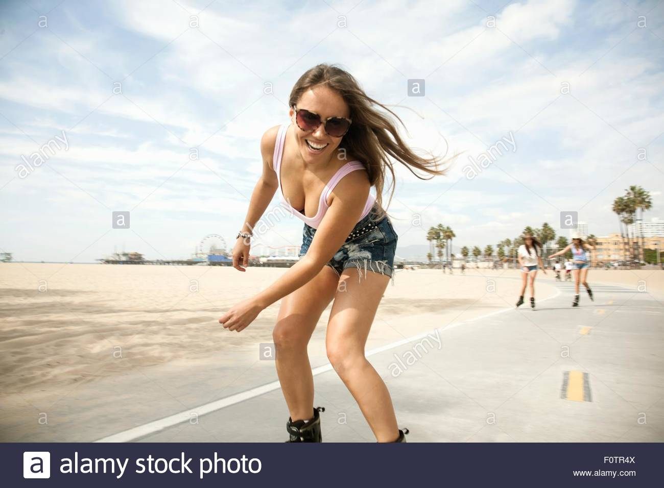 Portrait of young woman, outdoors, skating - Stock Image