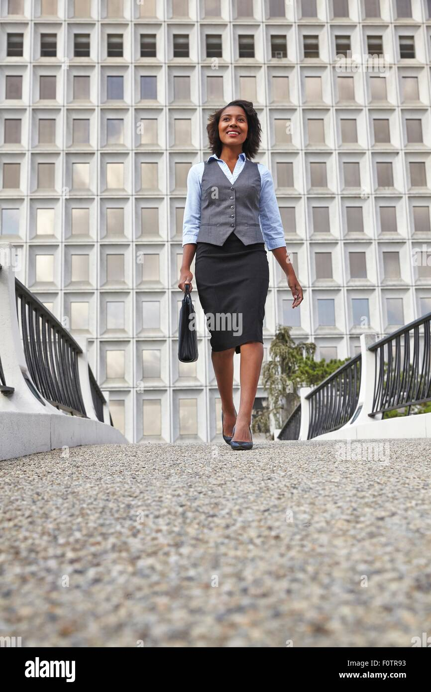 Low angle front view of business woman walking, carrying briefcase, smiling, looking away - Stock Image