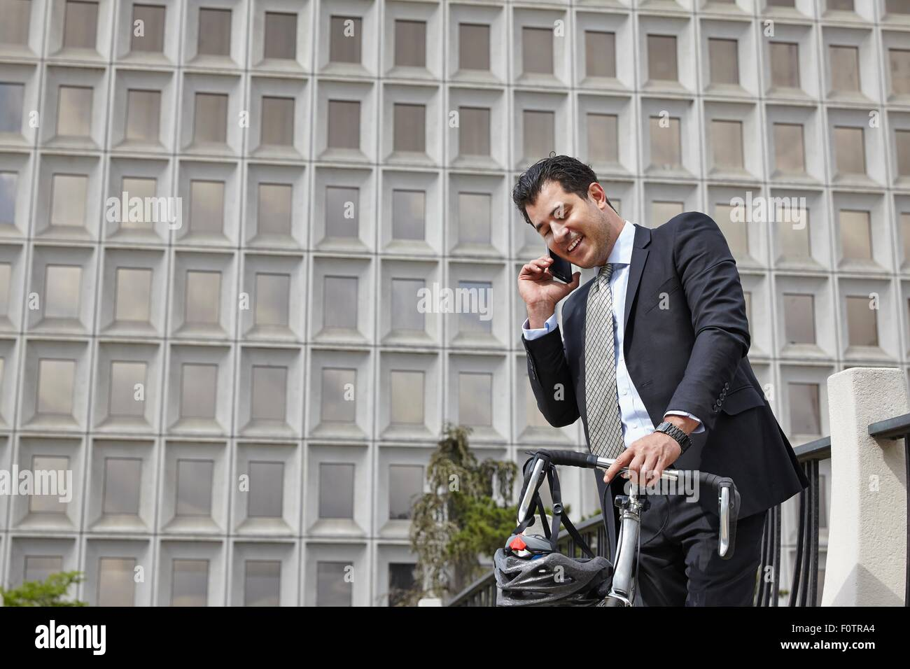 Mid adult business man holding bicycle, making telephone call using smartphone - Stock Image