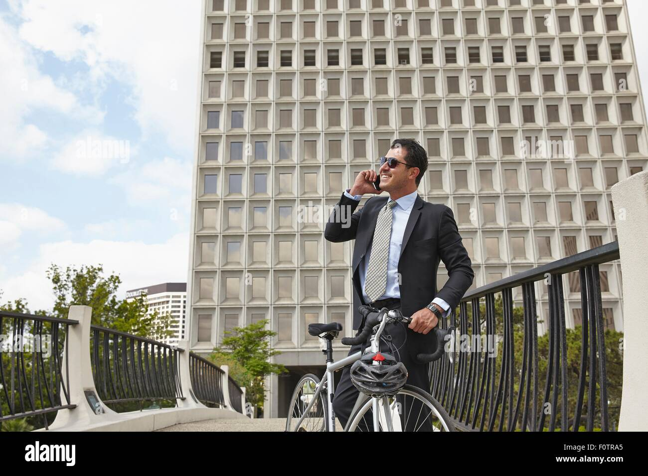 Mid adult business man holding bicycle, making telephone call using smartphone, wearing sunglasses - Stock Image