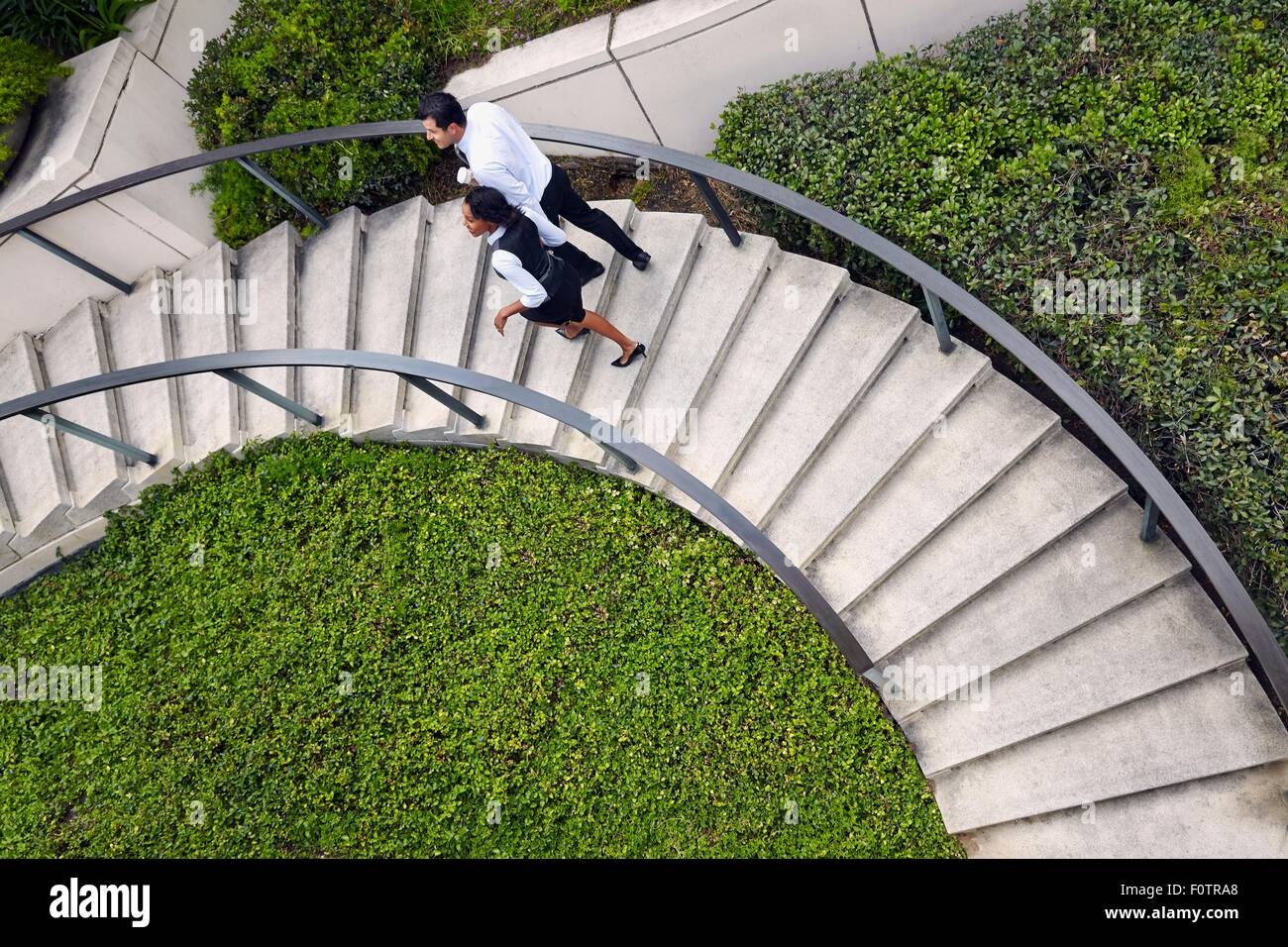 High angle view of business people ascending spiral stairway - Stock Image