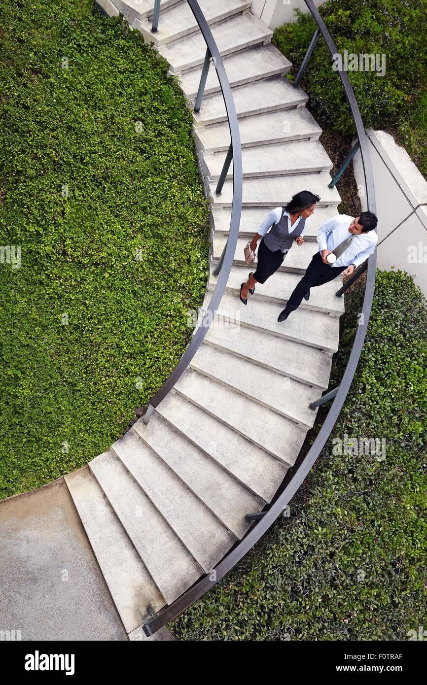 High angle view of business people descending spiral stairway - Stock Image