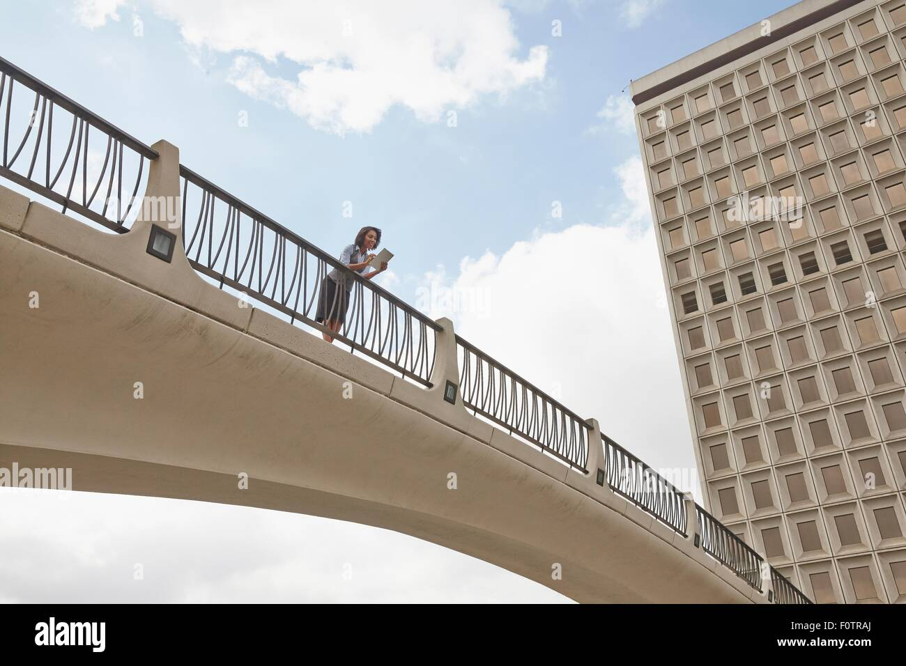 Low angle view of person on footbridge, City Hall East, Los Angeles, California, USA - Stock Image