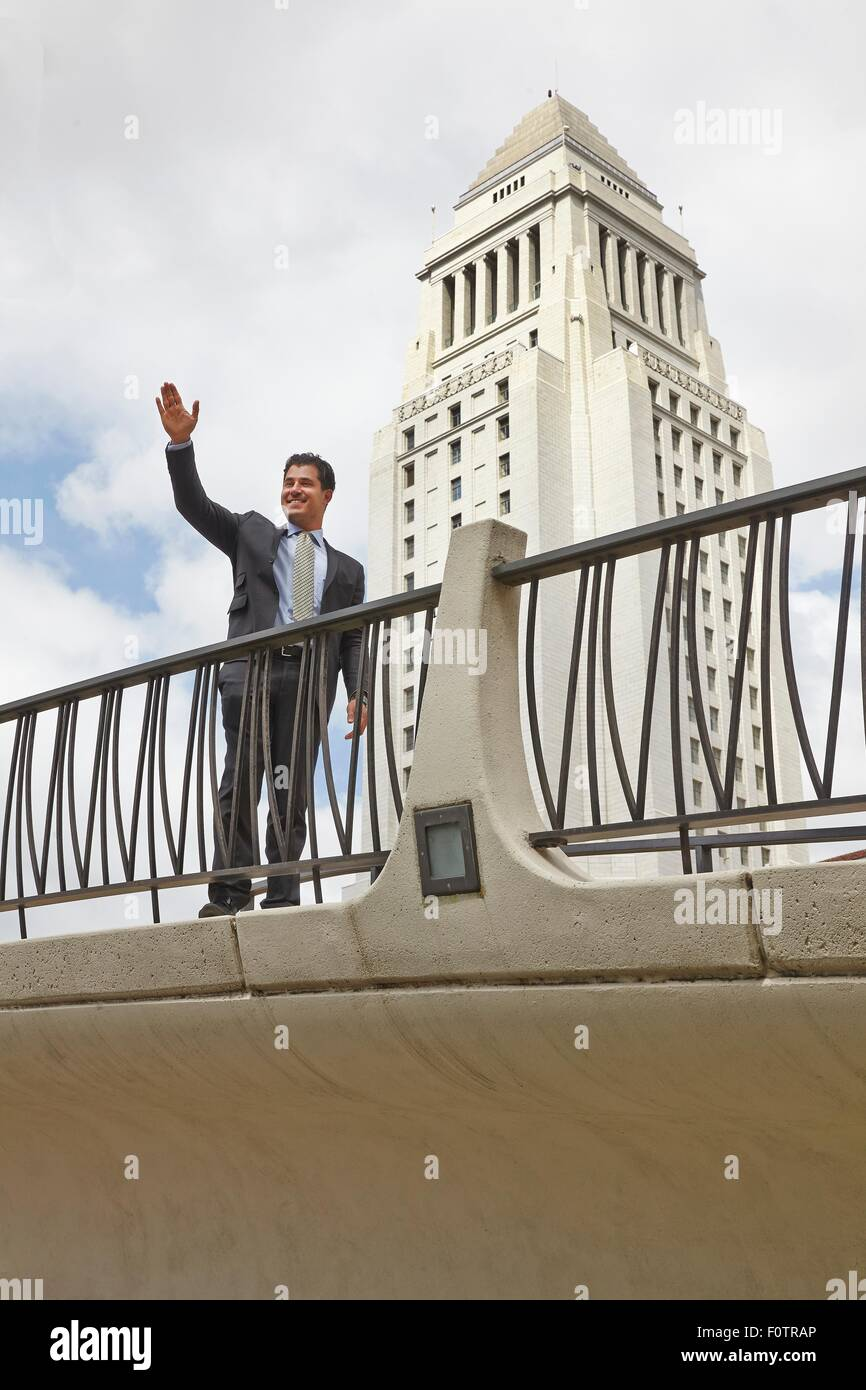 Business man standing on walkway, waving, smiling, Los Angeles City Hall, California, USA - Stock Image
