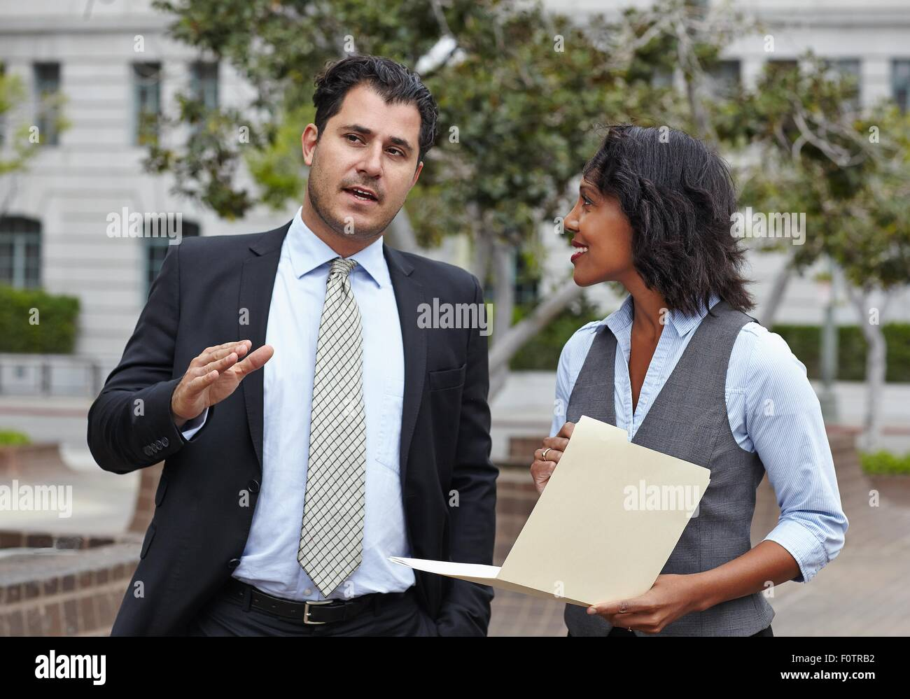Front view of business people discussing paperwork, waist up, looking away - Stock Image