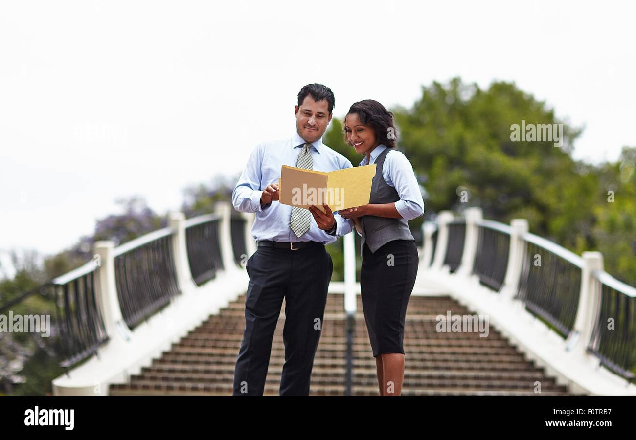 Business people standing in front of stairway looking at paperwork, smiling Stock Photo