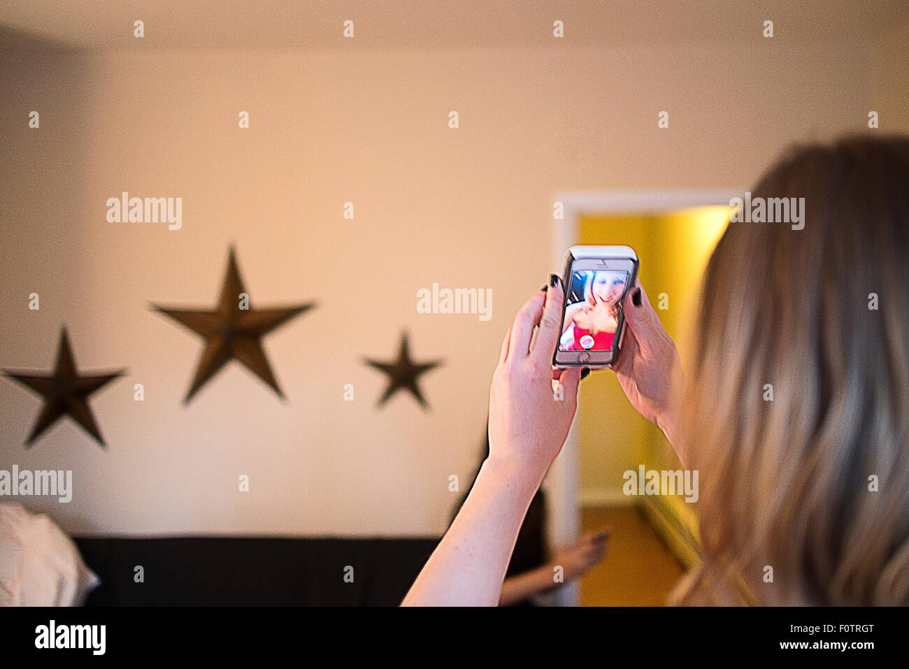 Over shoulder view of young woman taking smartphone selfie - Stock Image