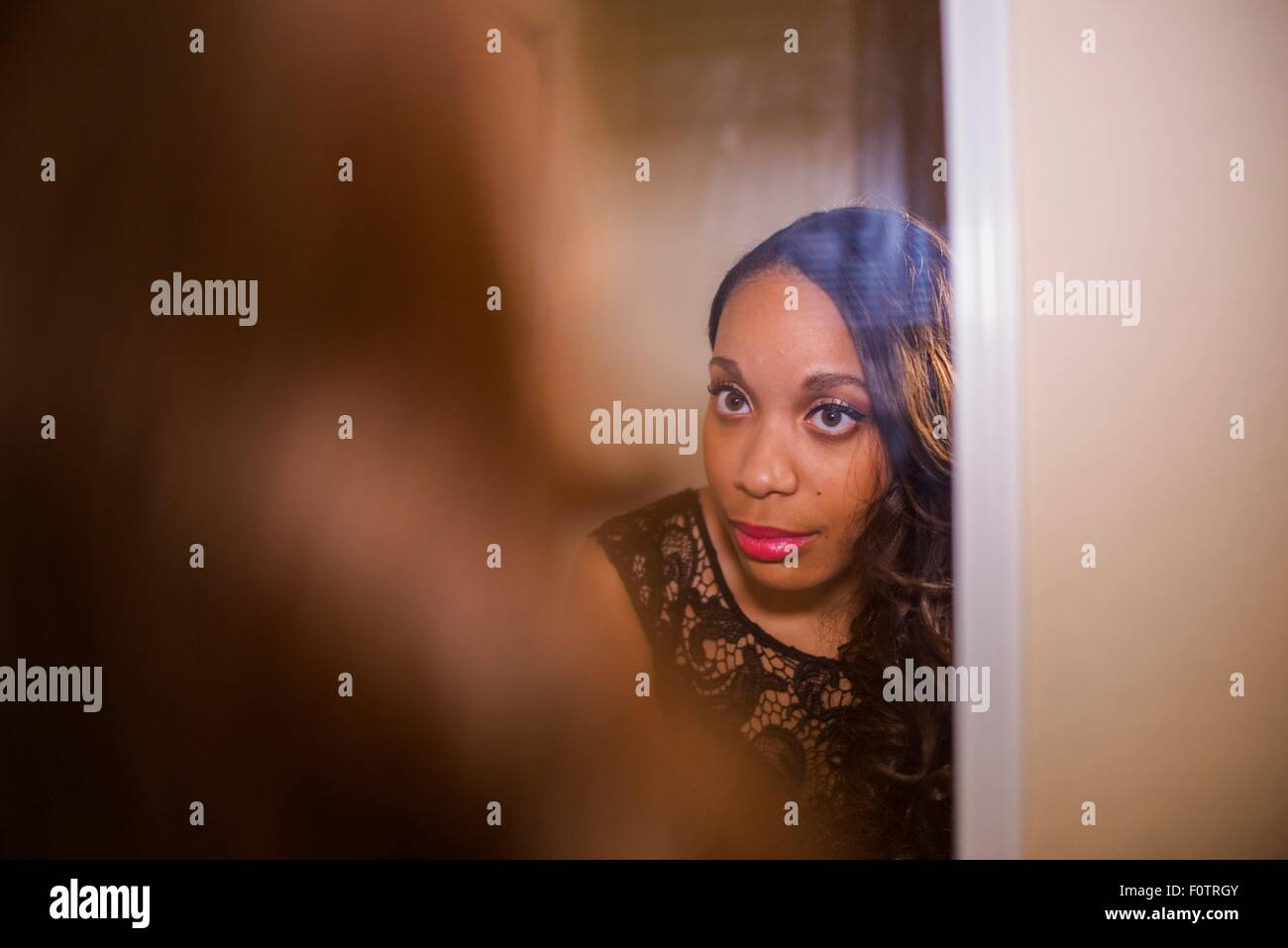 Young woman looking in wall mirror whist getting ready - Stock Image