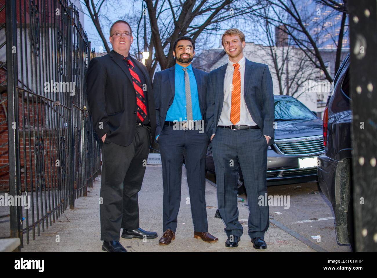 Portrait of three young male friends wearing suits for night out - Stock Image