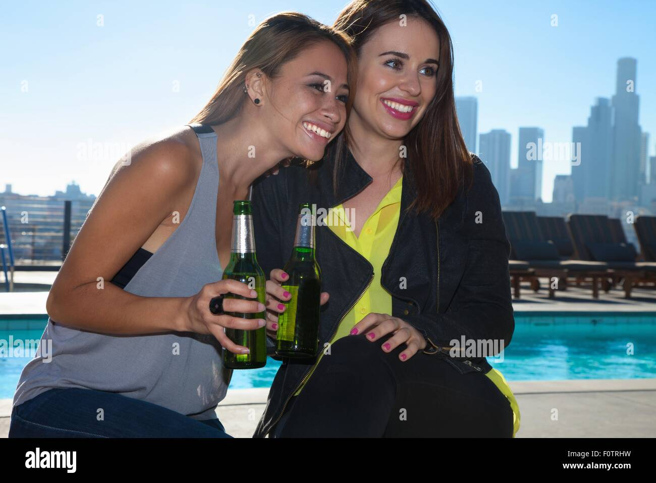 Portrait of two young female friends drinking beers at rooftop bar with Los Angeles skyline, USA - Stock Image