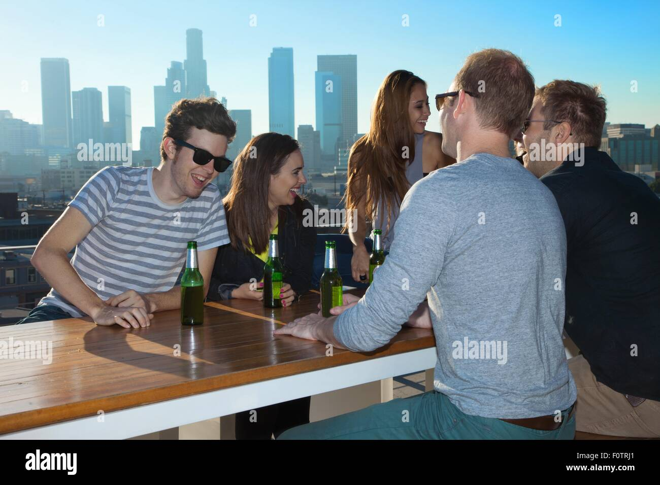Six adult friends talking and drinking beer at rooftop bar with Los Angeles skyline, USA - Stock Image