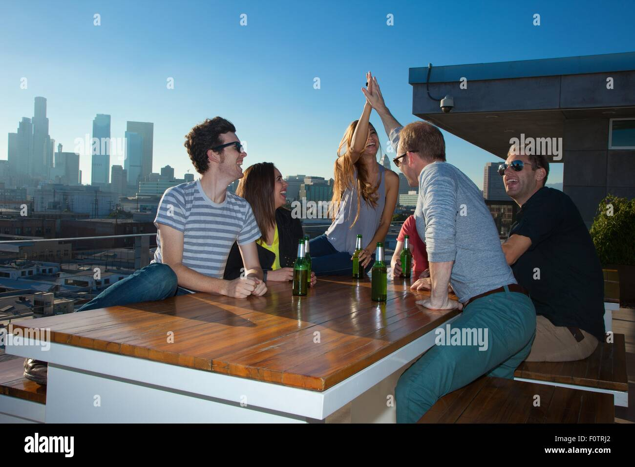 Six adult friends drinking beer at table of rooftop bar with Los Angeles skyline, USA - Stock Image