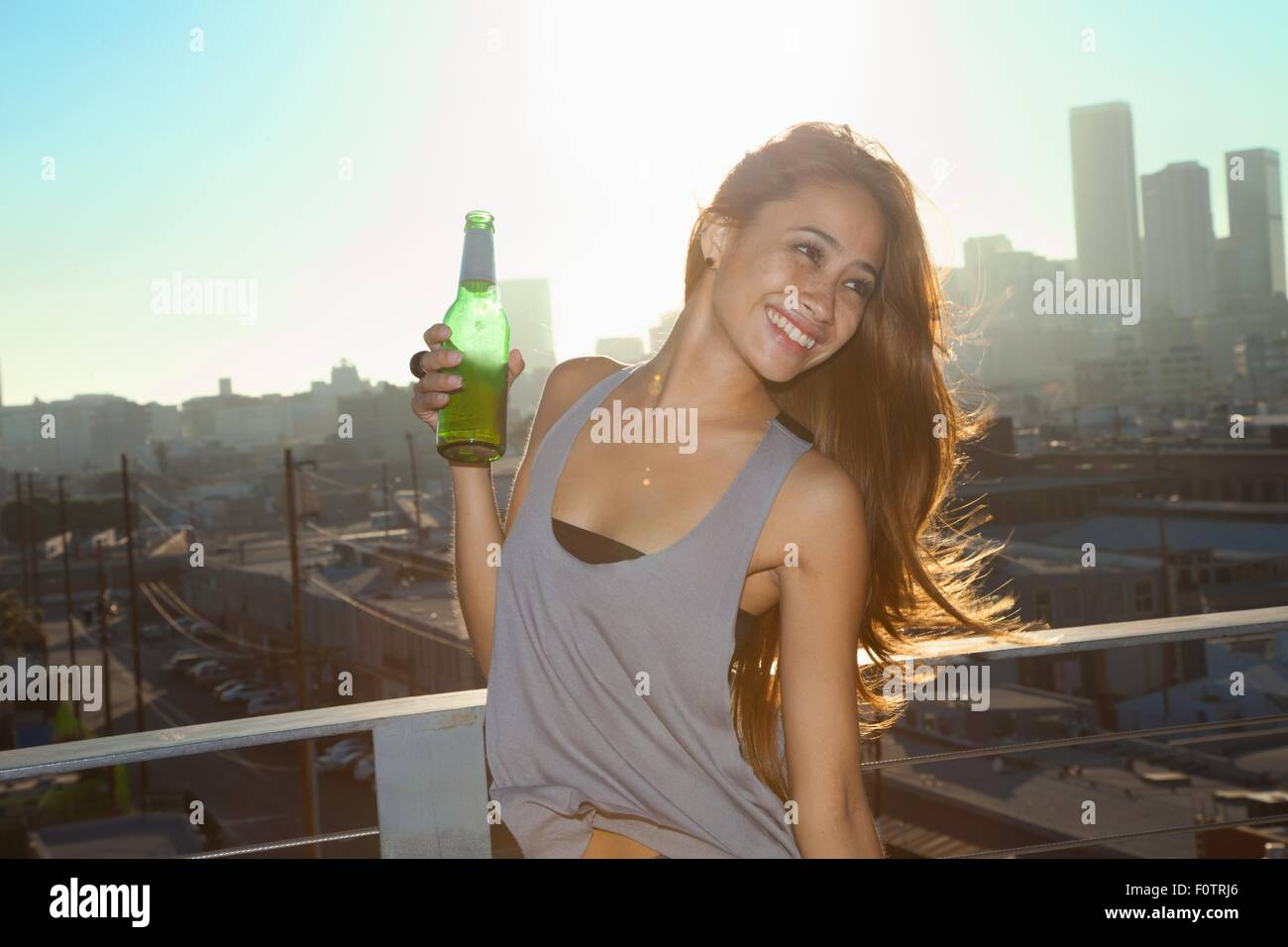 Portrait of young woman drinking beer on rooftop bar with Los Angeles skyline, USA - Stock Image