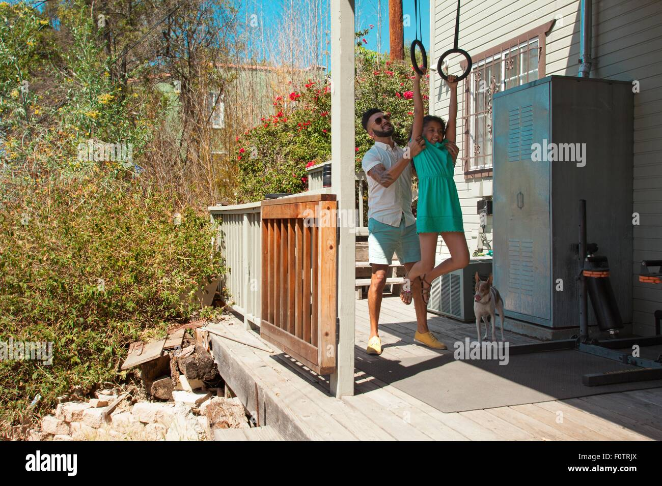 Mid adult man lifting daughter onto exercise rings on patio - Stock Image