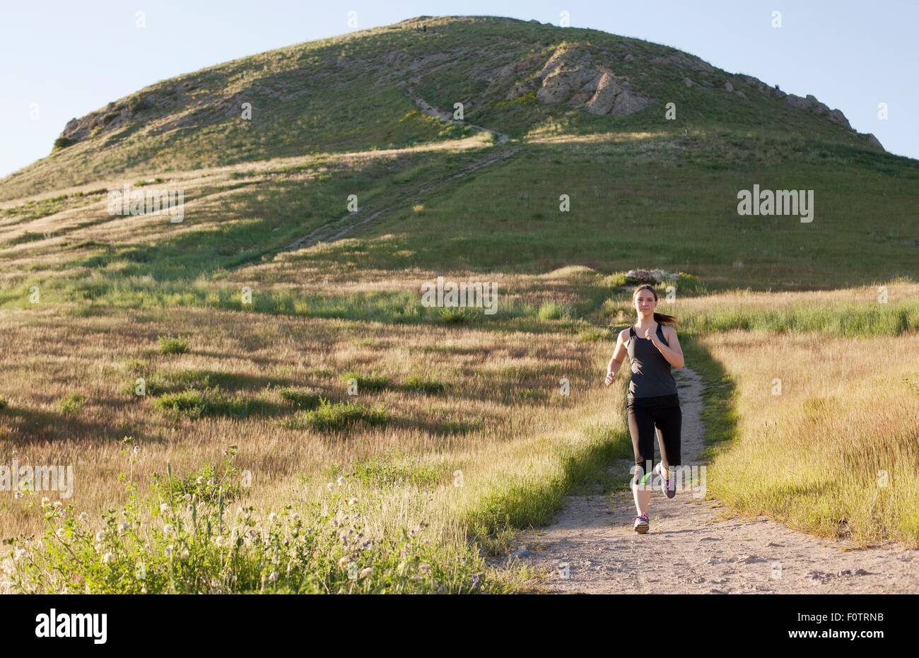 Young woman running on hillside track - Stock Image