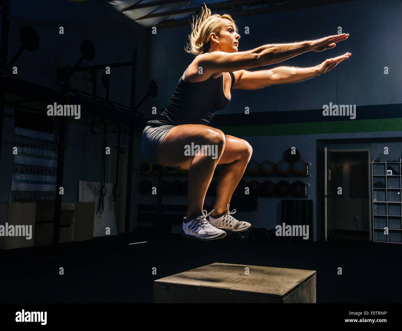 Young woman jumping mid air on gym box with arms reaching out - Stock Image