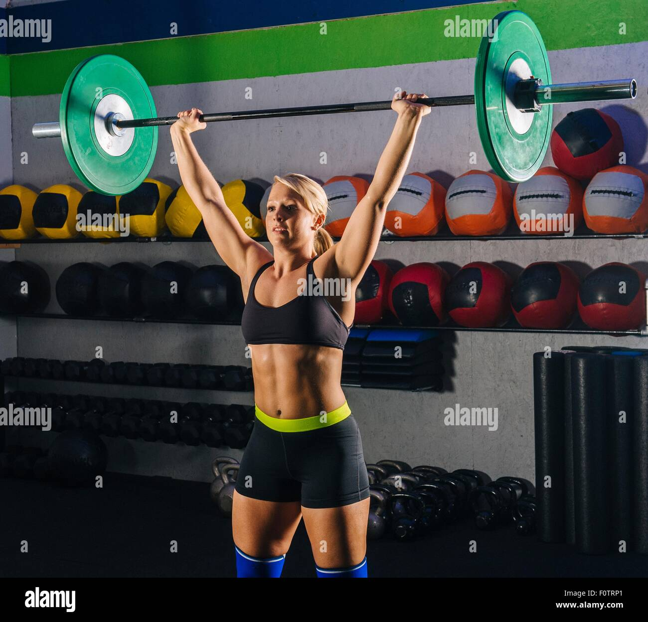 Young woman weight lifting with barbell in gym - Stock Image