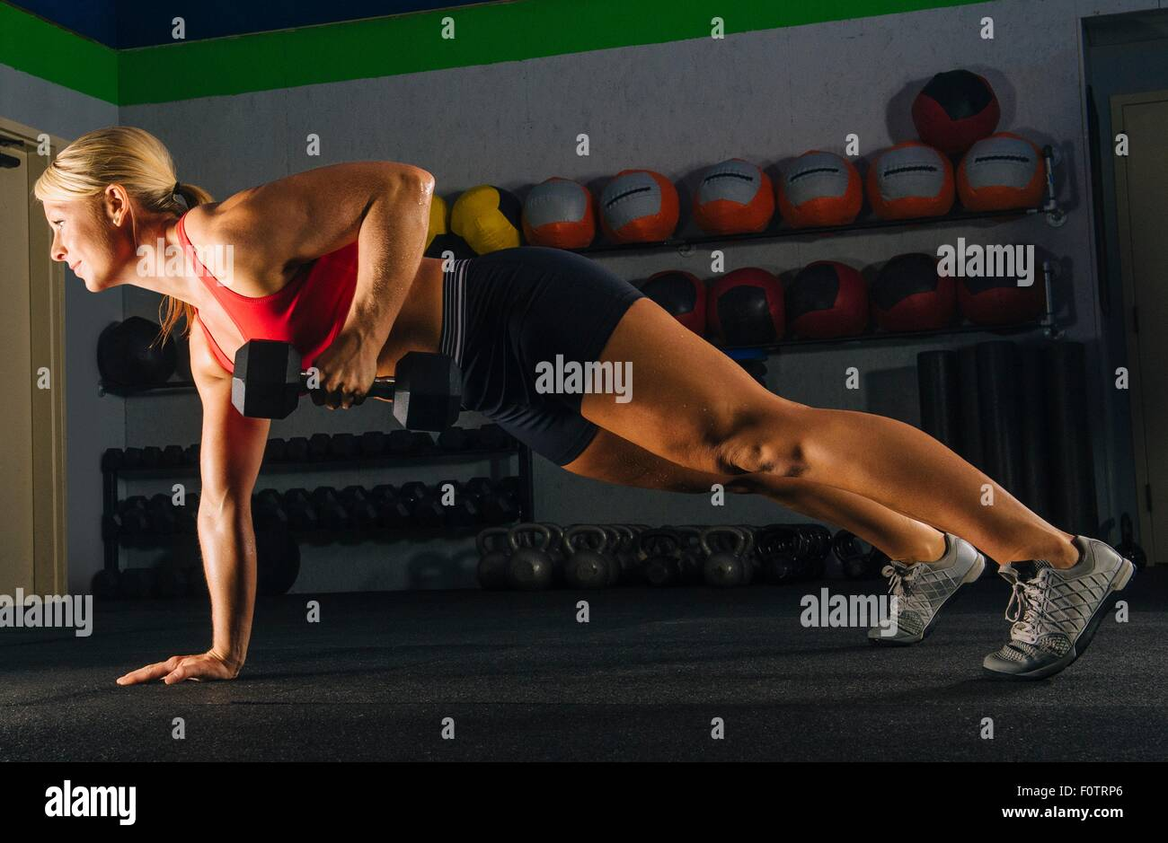 Young woman doing one arm push up in gym - Stock Image