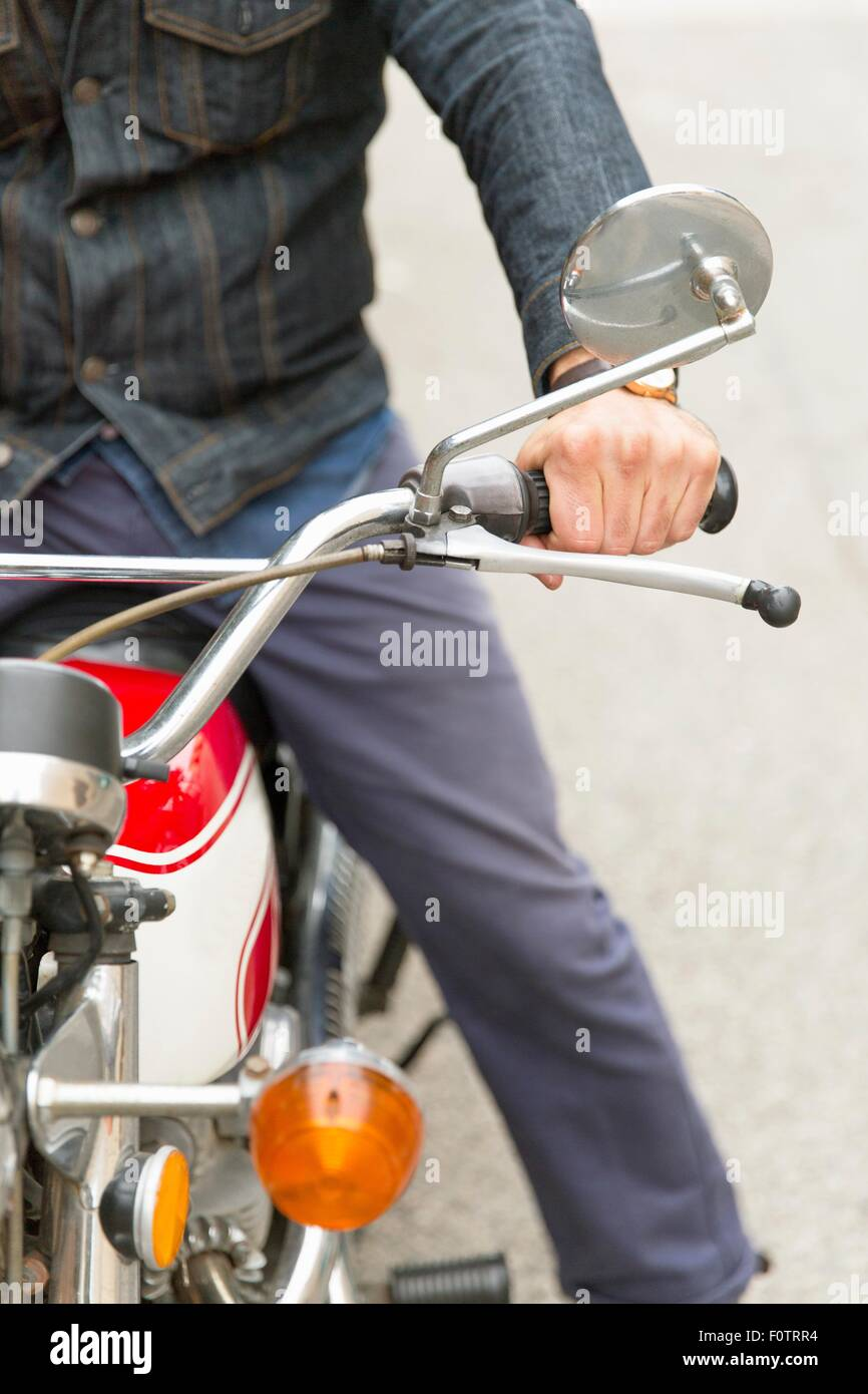 Mid adult man on motorbike, mid section - Stock Image