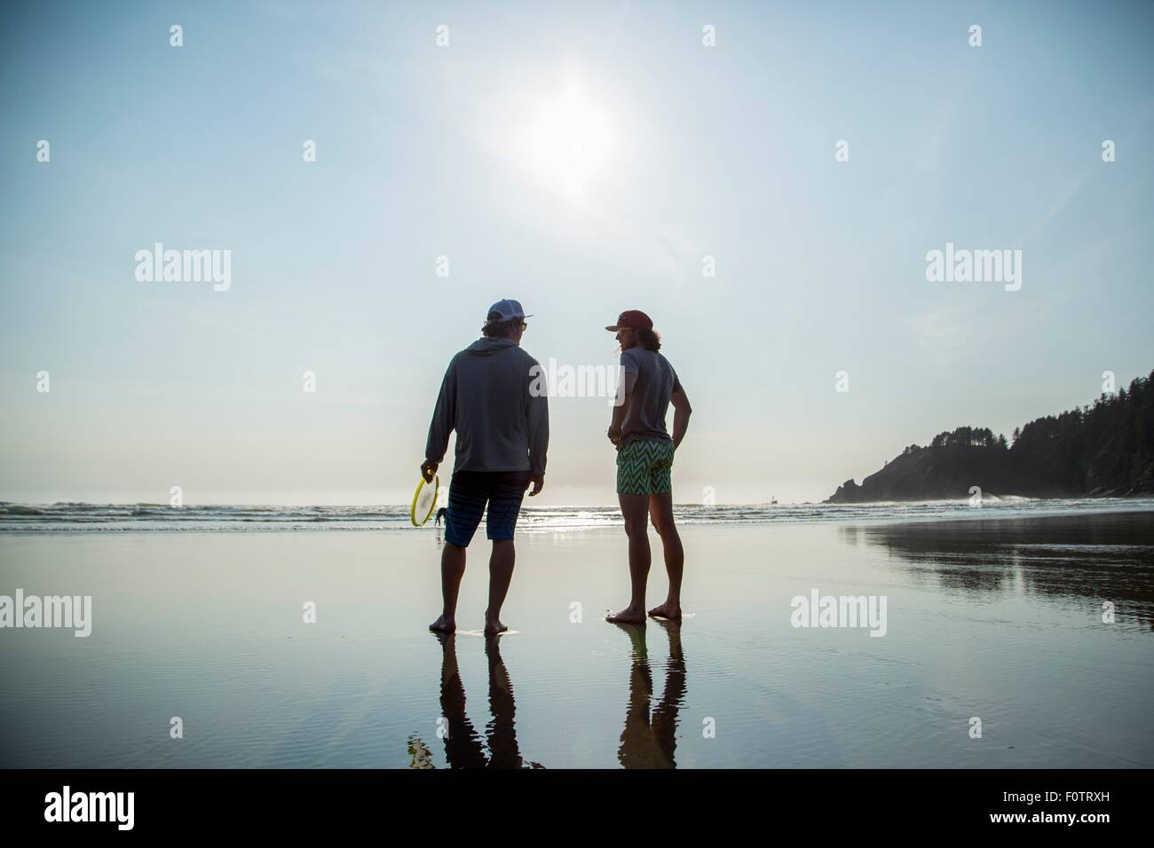 Rear silhouetted view of two young men chatting on Short Sands Beach, Oregon, USA Stock Photo