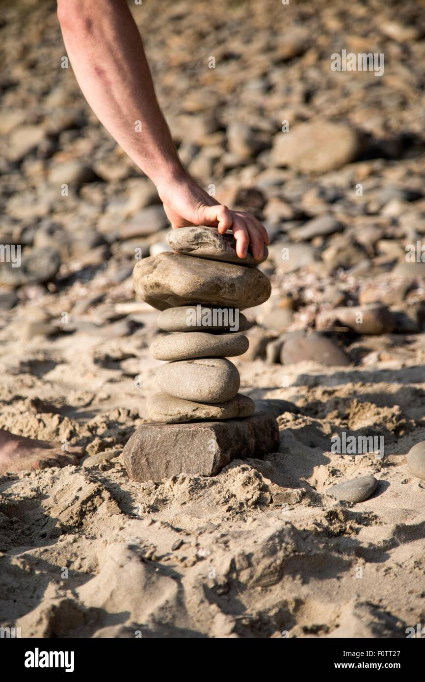 Hand of young man placing stone on stone stack at beach - Stock Image