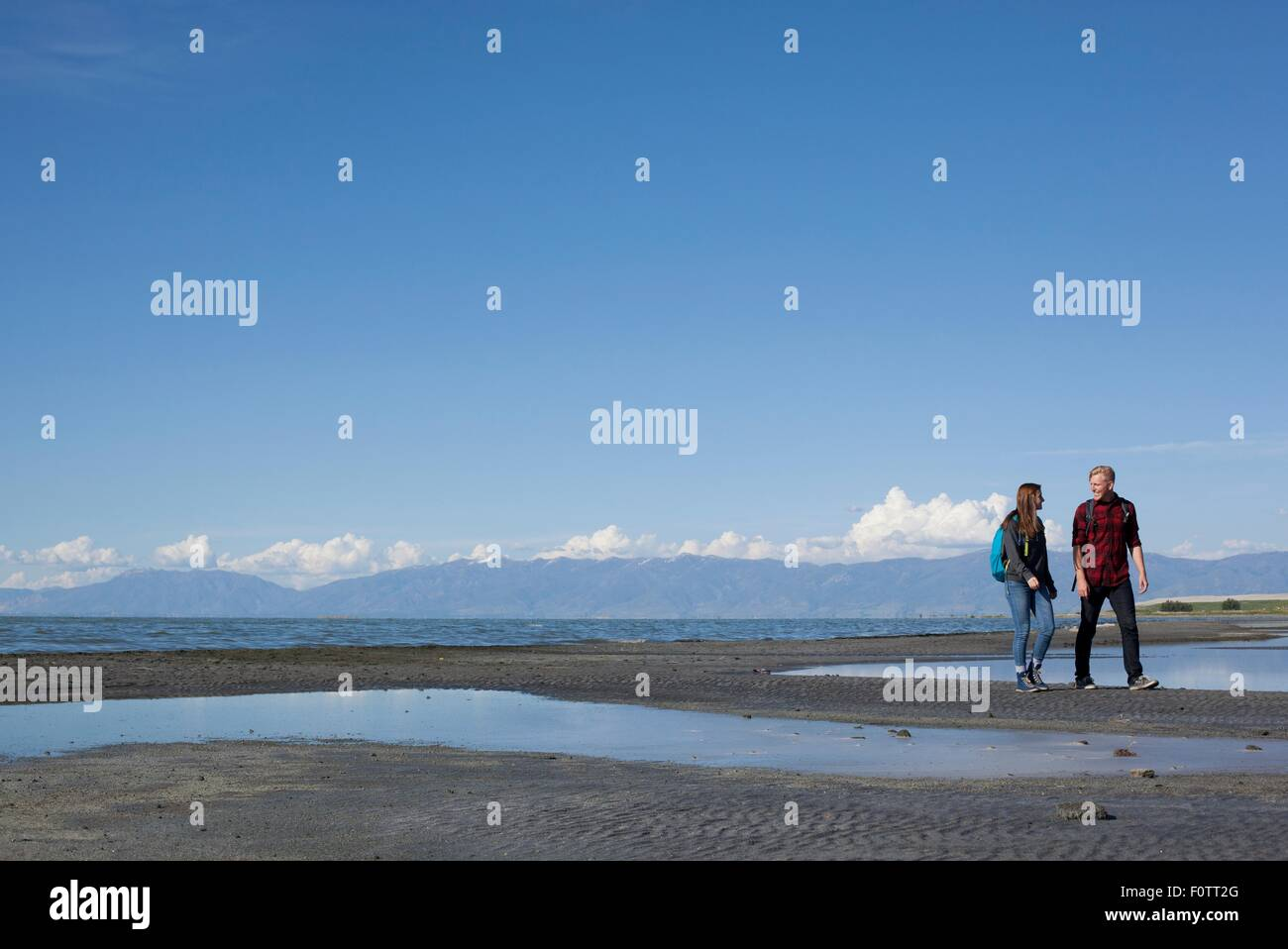 Young couple walking, looking at each other, Great Salt Lake, Utah, USA - Stock Image