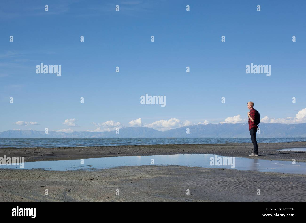 Side view of young man standing at waters edge looking out, Great Salt lake, Utah, USA - Stock Image