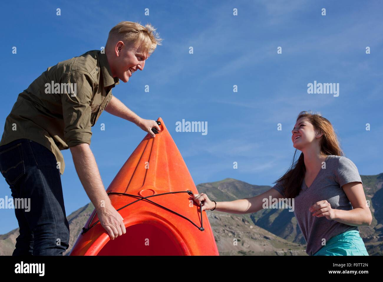 Young couple preparing orange kayak, looking at each other smiling - Stock Image