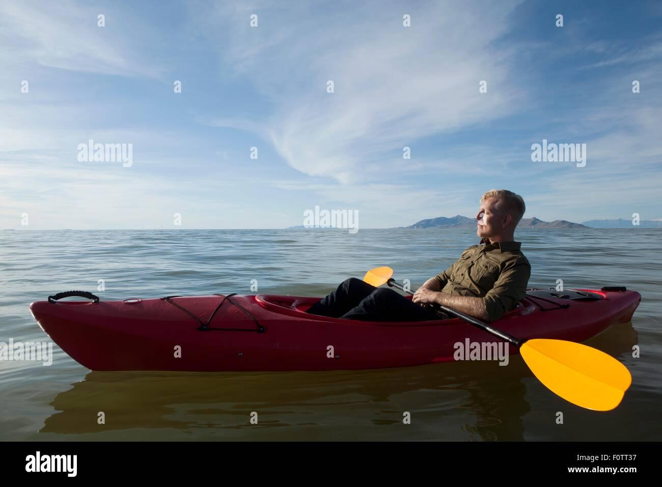Side View Of Young Man In Kayak On Water Holding Paddles Eyes Closed Great Salt Lake Utah USA